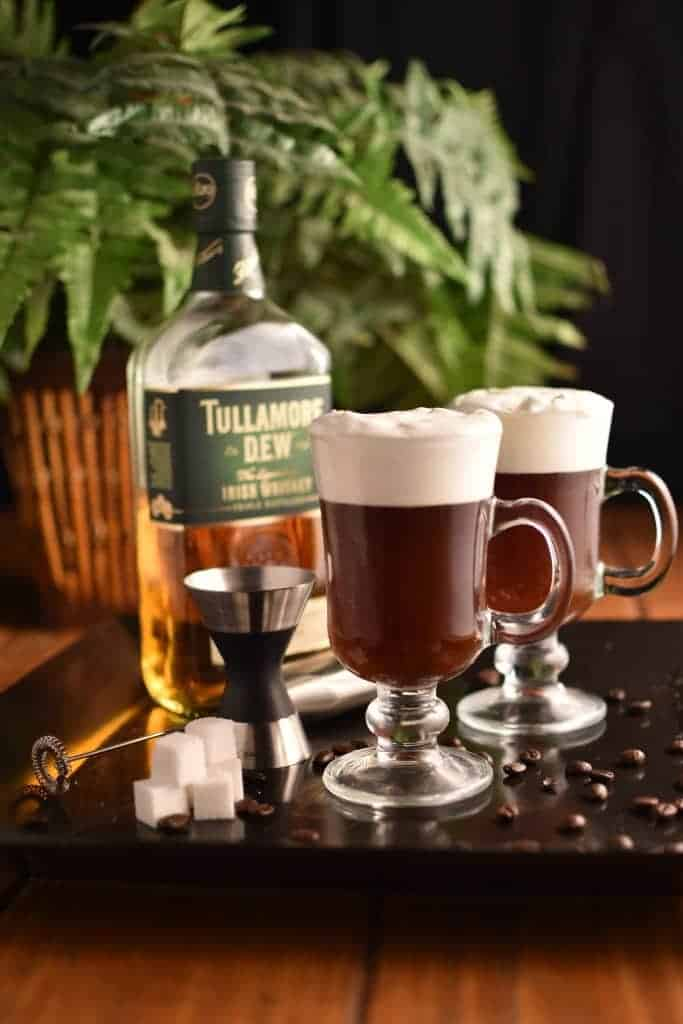 Two glasses of Irish coffee with a bottle of whiskey