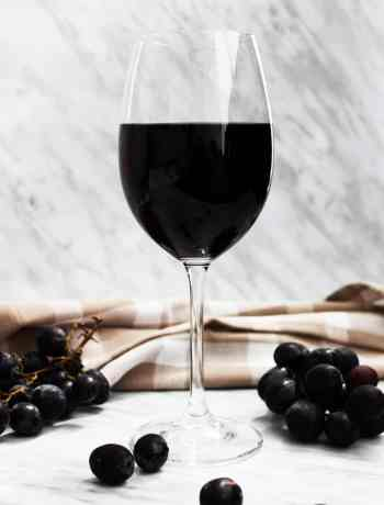 A glass of red wine on a marble backdrop with bunches of grapes