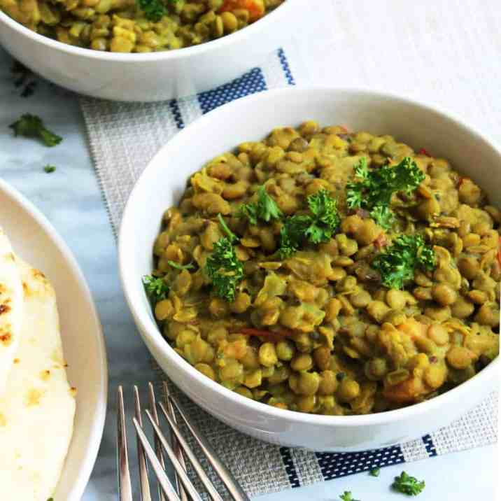 A bowl of green lentil daal with two forks on a white and blue mat