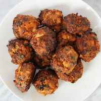 An overhead shot of cooked lamb meatballs on a white plate