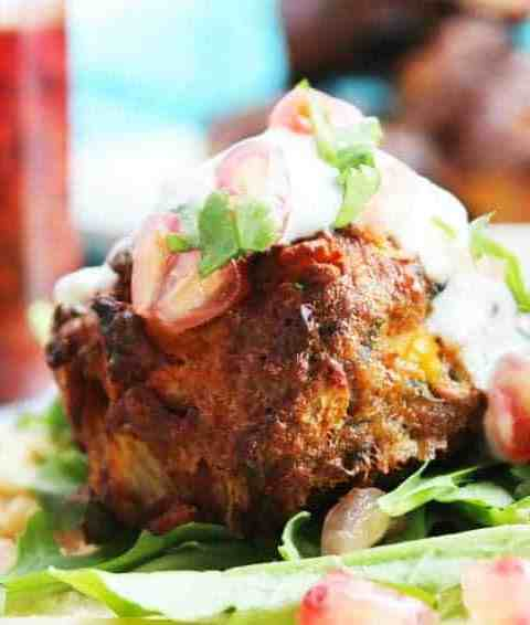 A closeup of a lamb meatball with tzatziki and pomegranate seeds