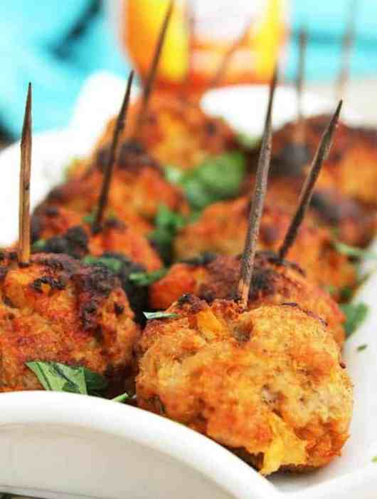 Closeup of baked pork meatballs on a white serving plate