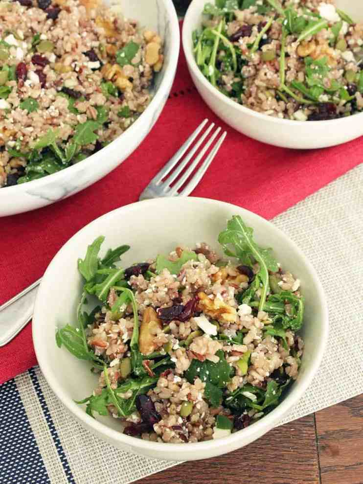 two small bowls of brown rice salad next to a large serving bowl