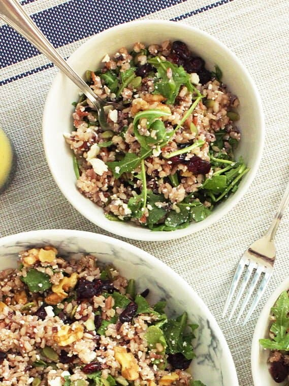Op down shot of a small bowl of brown rice salad with a fork