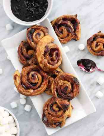 Top down shot of sweet puff pastry pinwheels on a white serving tray