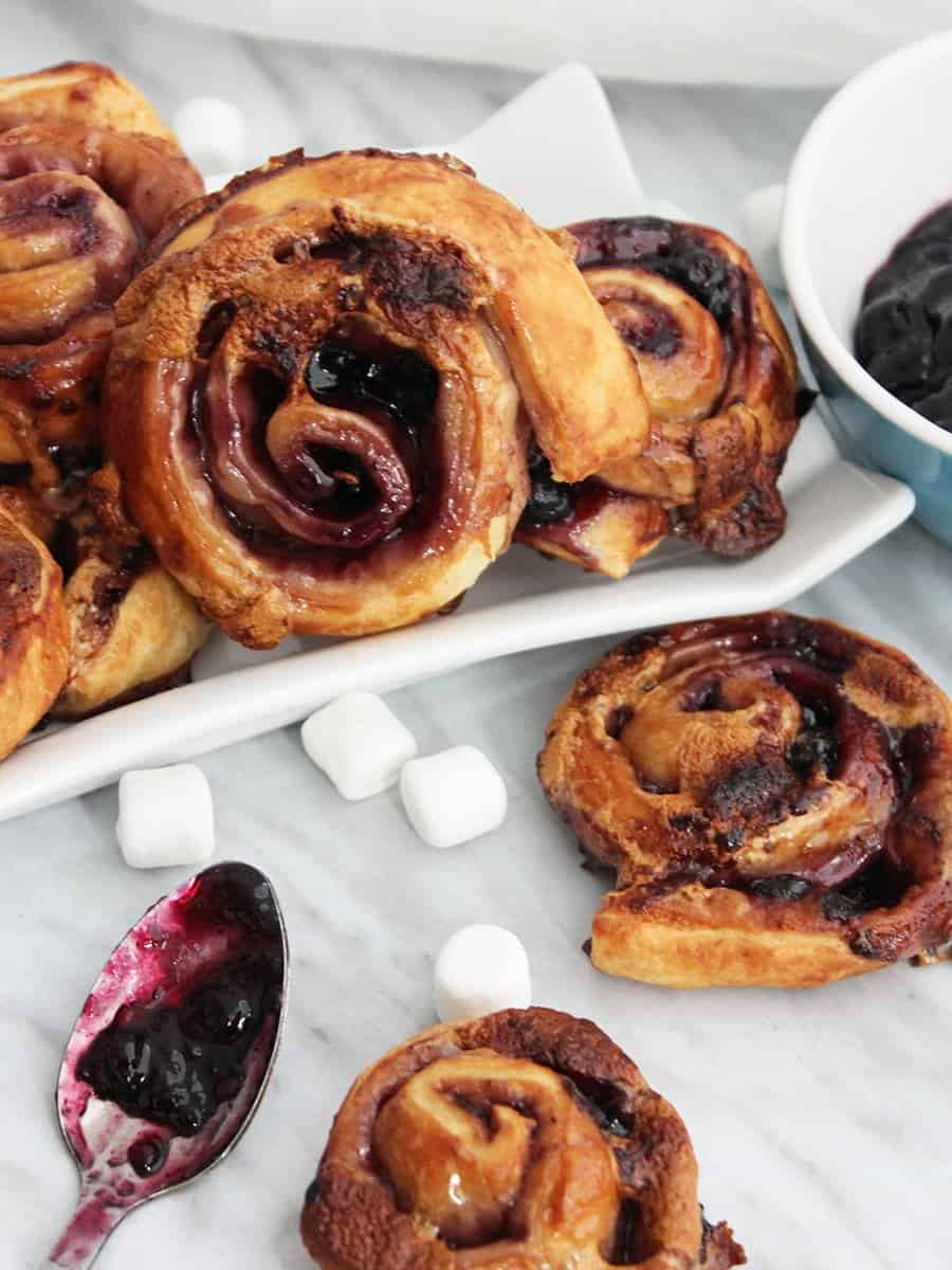Close up of a sweet puff pastry pinwheel next to a spoon with jam