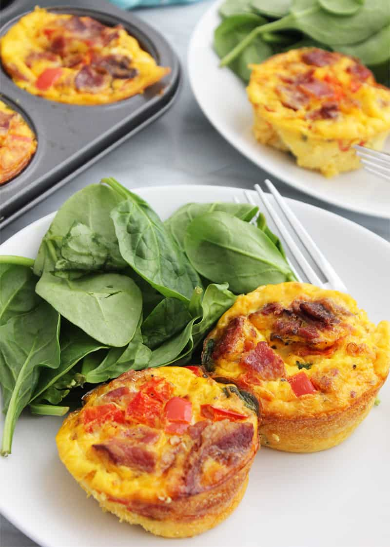 Two egg muffins on a white plate with fresh spinach