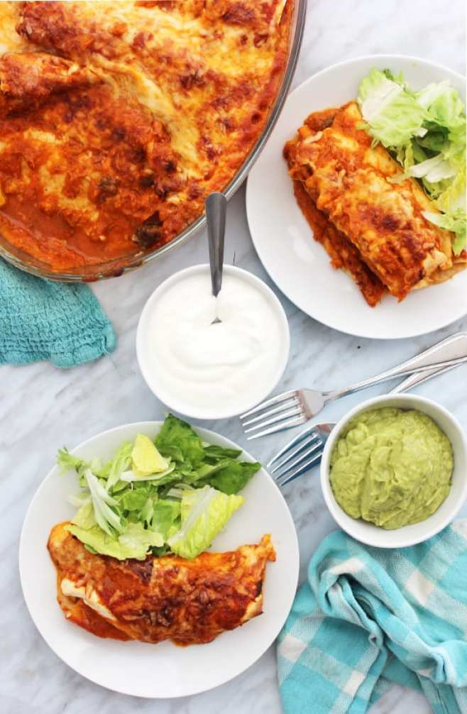 Top down shot of enchiladas served with sour cream and guacamole