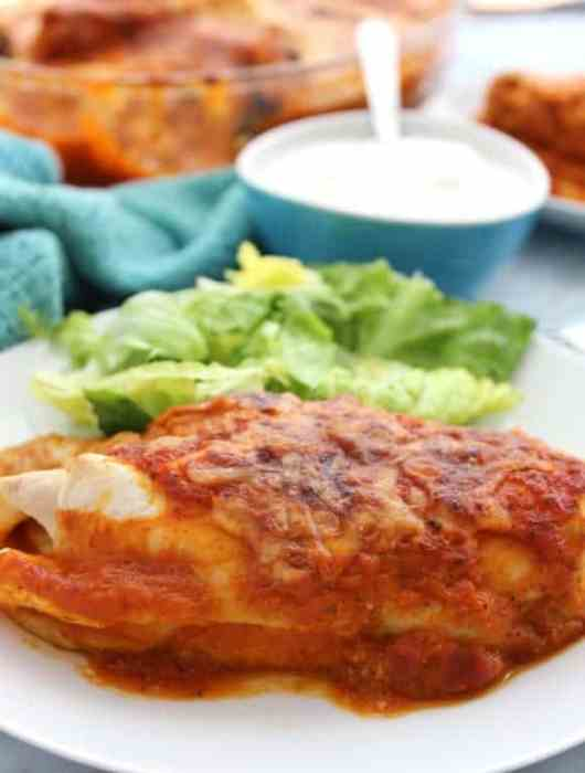 An enchilada on a white plate with sour cream