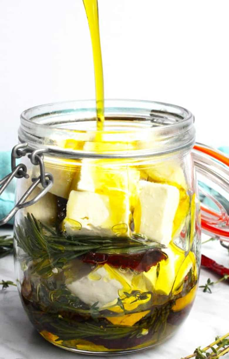 Oil being poured over feta and herbs