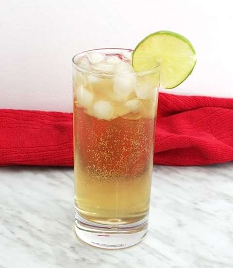 A spiced rum cocktail, garnished with lime, on a marble work top.
