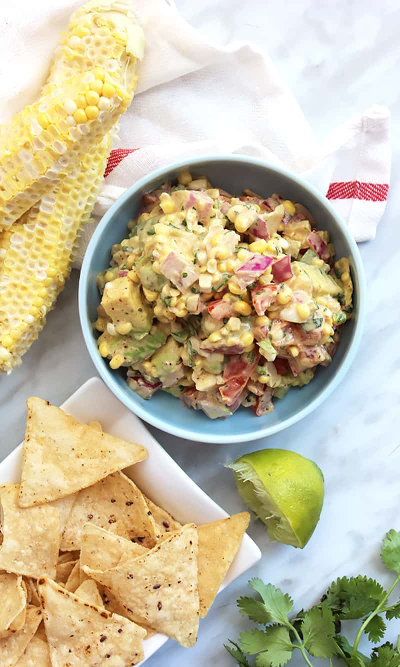 A bowl of corn salsa serves with tortilla chips