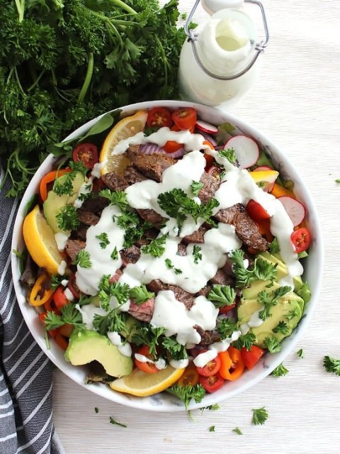 A bowl of steak salad on a white surface