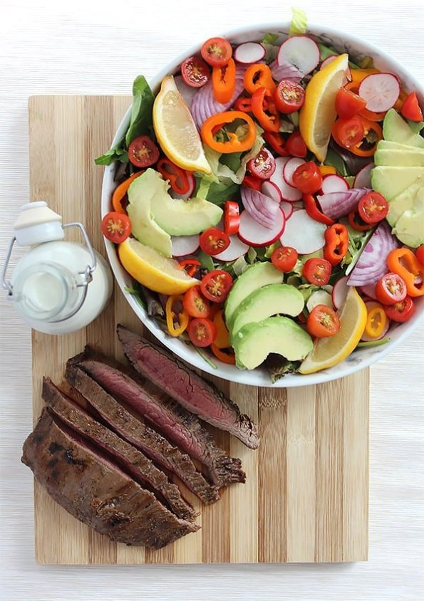 A bowl of salad and sliced flank steak and a bottle of dressing on a chopping board