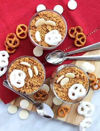 Top shot of there chocolate pots topped with pretzels on a wooden chopping board