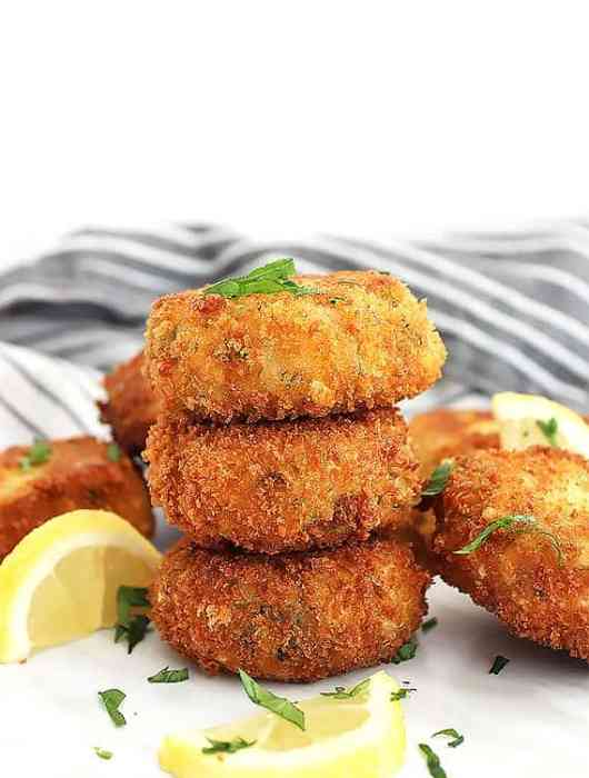 Stacked mini crab cakes garnished with fresh herbs