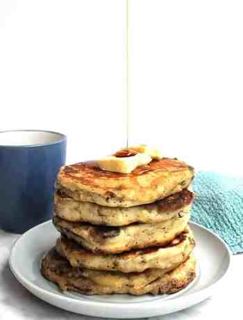 A stack of savory pancakes on a plate with maple syrup being drizzled on top