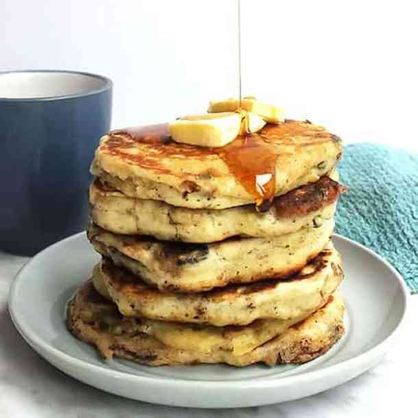 A stack of savory pancakes with butter and maple syrup