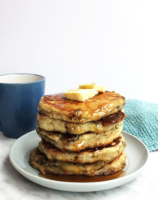 A stack of savory pancakes with a pat of butter on top