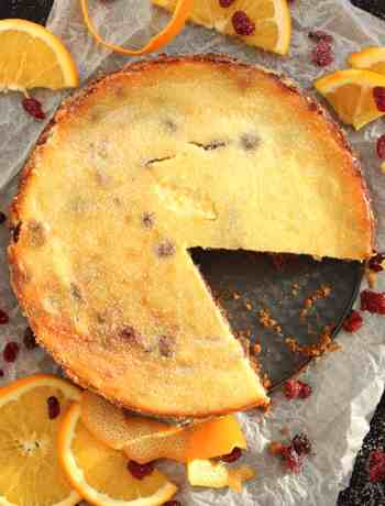 A cranberry and orange cheesecake with a slice cut of of it