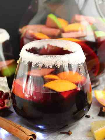 A glass of red wine sangria in front of a jug