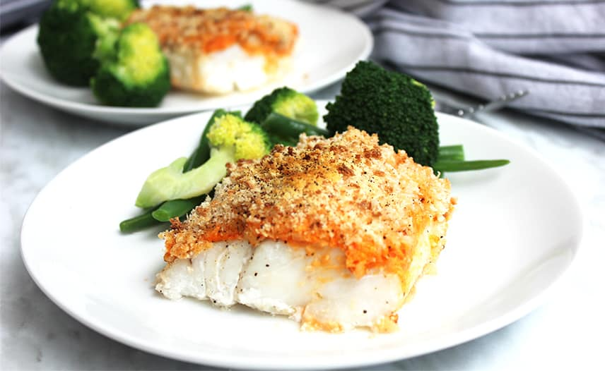Crispy baked cod served on a white plate with green veggies
