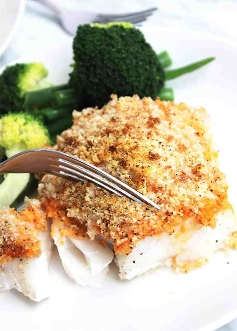 A piece of crispy baked cod being cut into with a fork