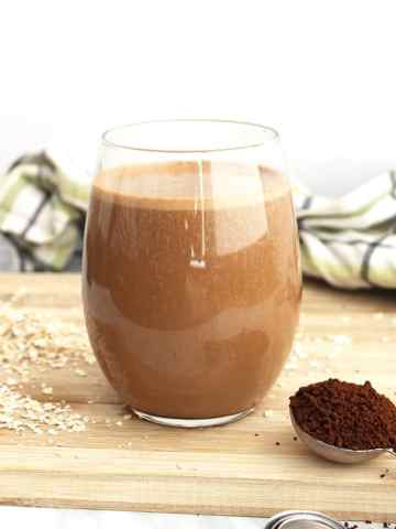 A glass with a smoothie next to ground coffee and oats on a board