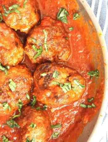 Bison meatballs in a skillet with tomato sauce