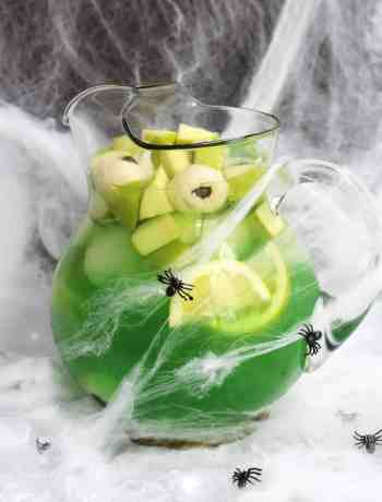 Halloween sangria in a large jusg decorated with cobwebs and plastic spiders.