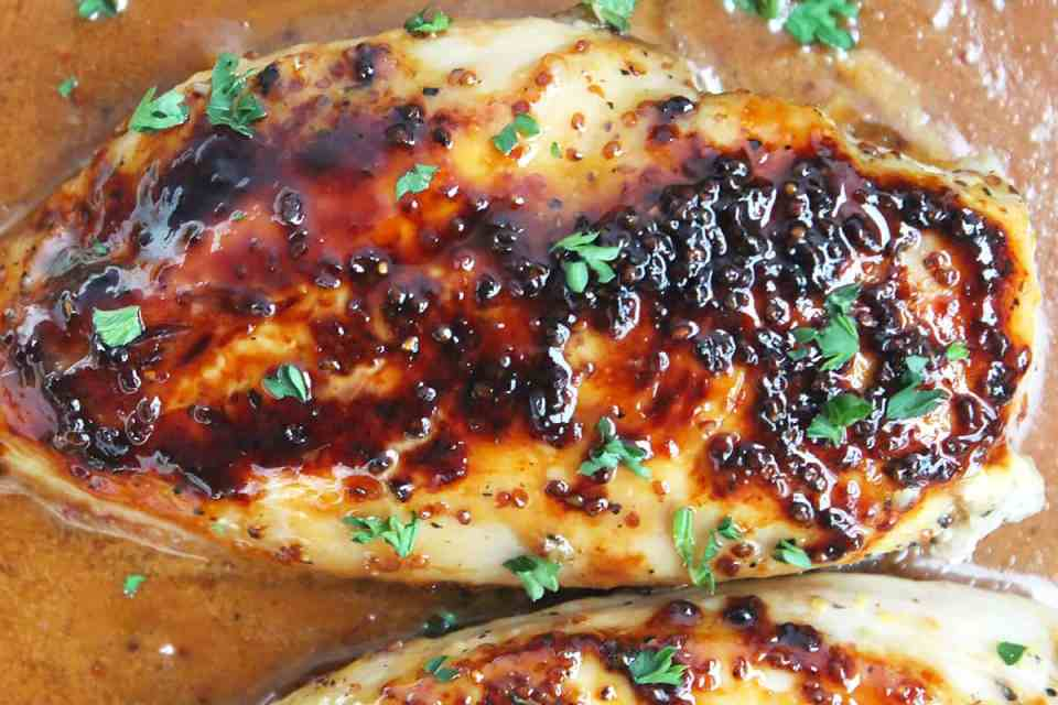 Overhead shot of a honey and mustard chicken breast sitting in sauce.