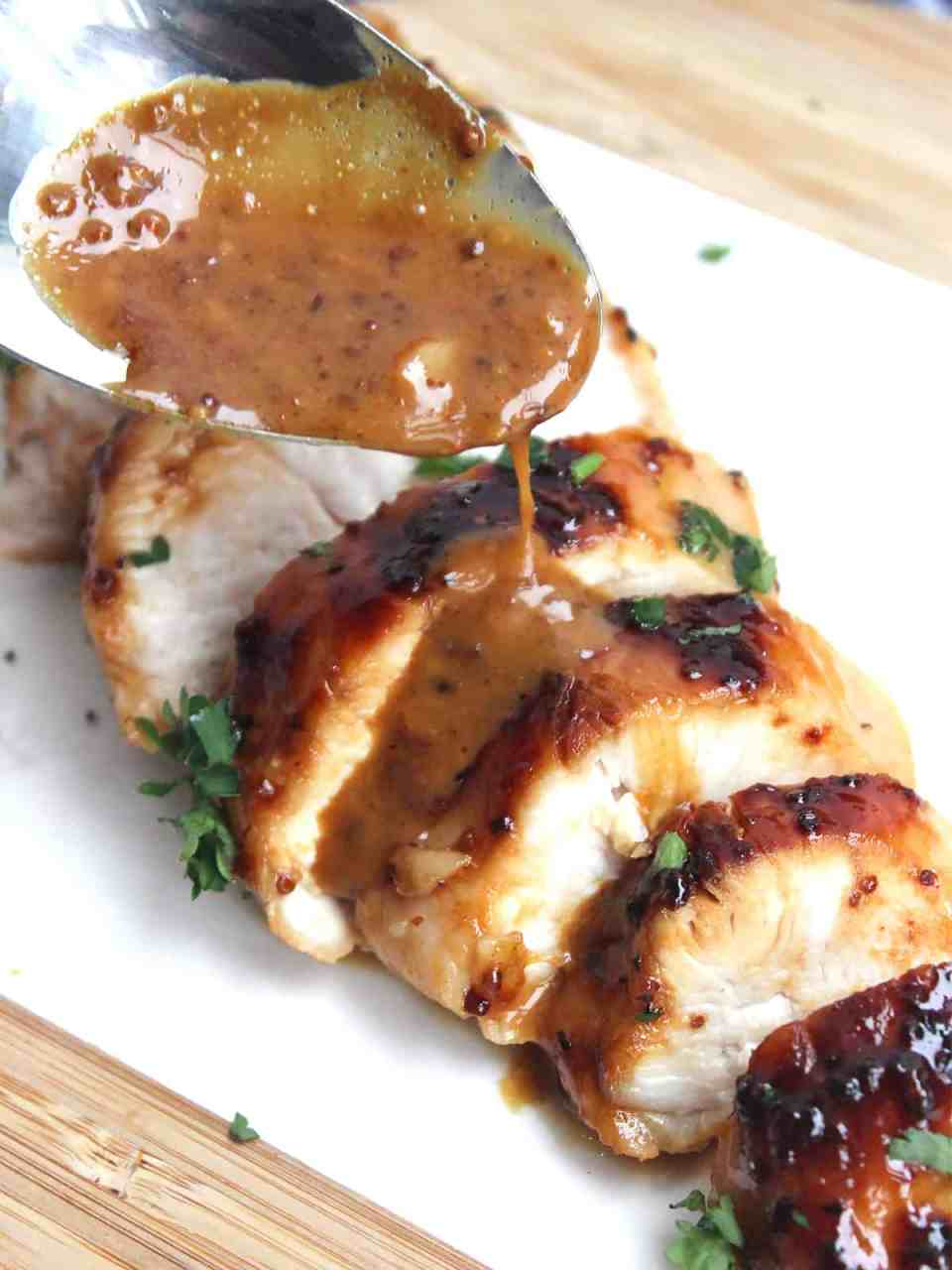 Sauce on a spoon being drizzled over the sliced chicken breast.