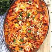 Tomato and beef pasta bake in a glass dish topped with melted cheese.