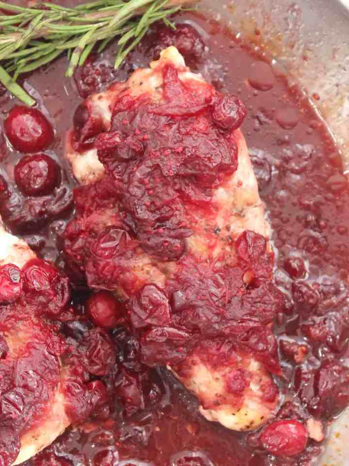 Close up of the cranberry sauce on top of a baked chicken breast.