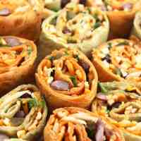 Close up of eight Mexican pinwheels filled with cheese and sprinkled with fresh cilantro.