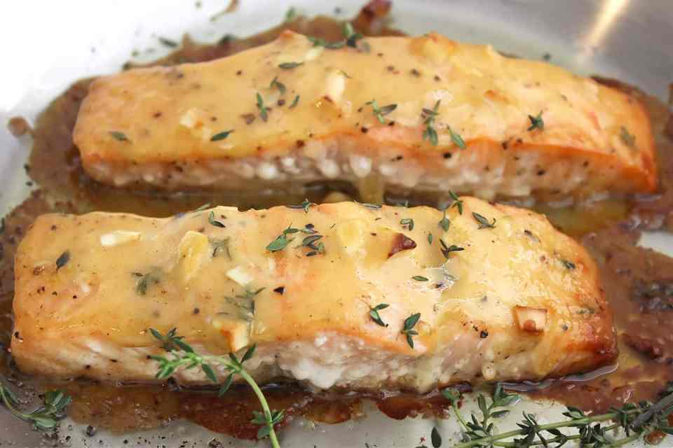 Close up of two baked salmon fillets garnished with fresh thyme.
