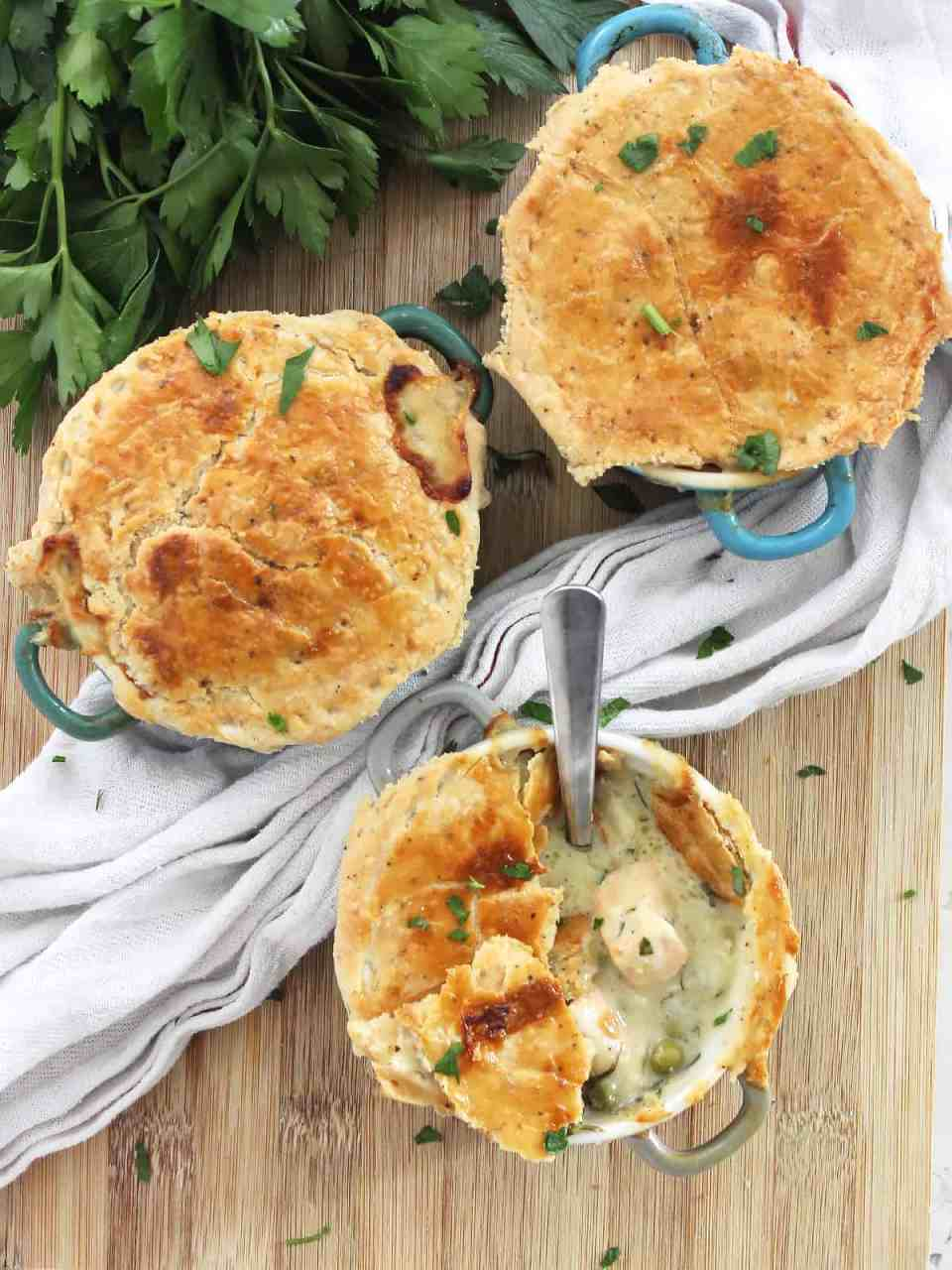 Three salmon pies on a wooden chopping board with fresh parsley.