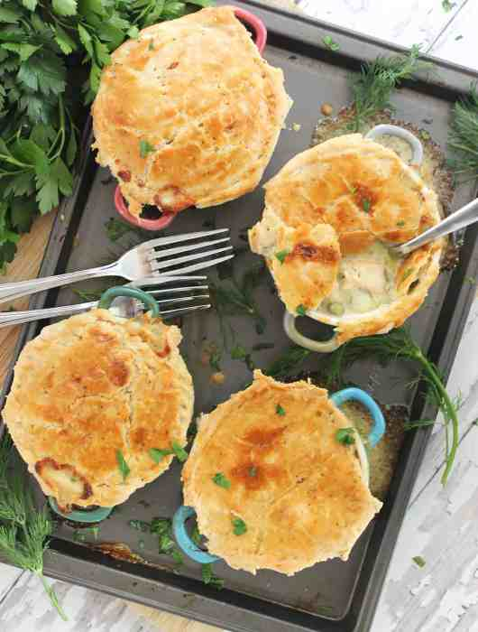 Four baked salmon pot pies on a baking sheet, garnished with fresh dill and parsley.
