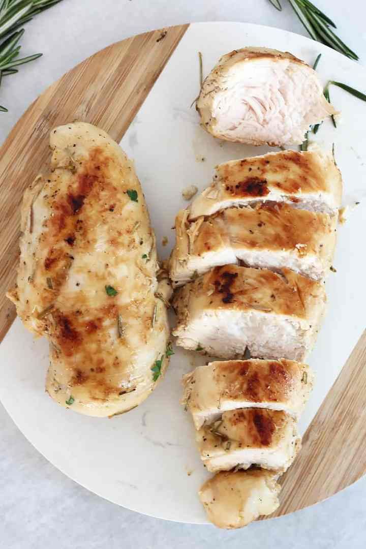 Two cooked chicken breasts on a chopping board. One sliced and the other whole.