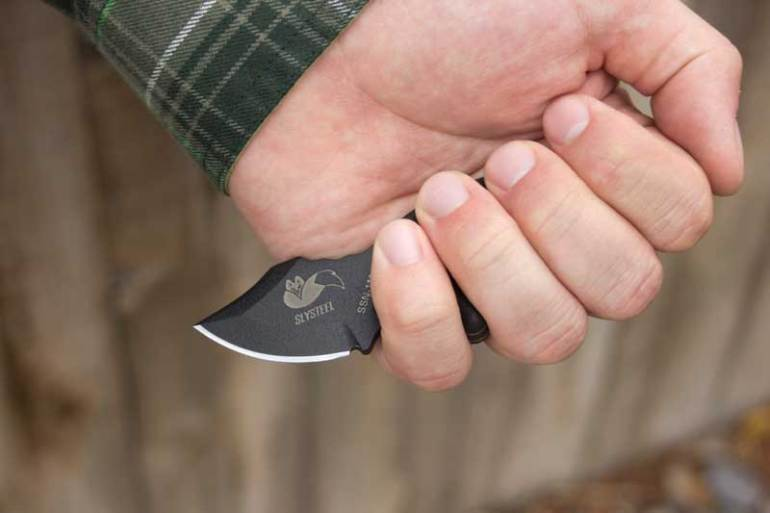A photograph of a single edge Final Option Blade deployed in reverse grip with palmed fist.