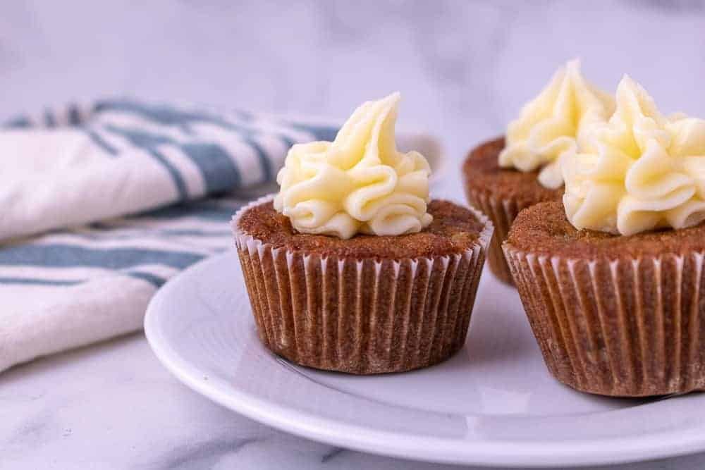 3 Carrot cake cupcakes on a plate with cream cheese frosting