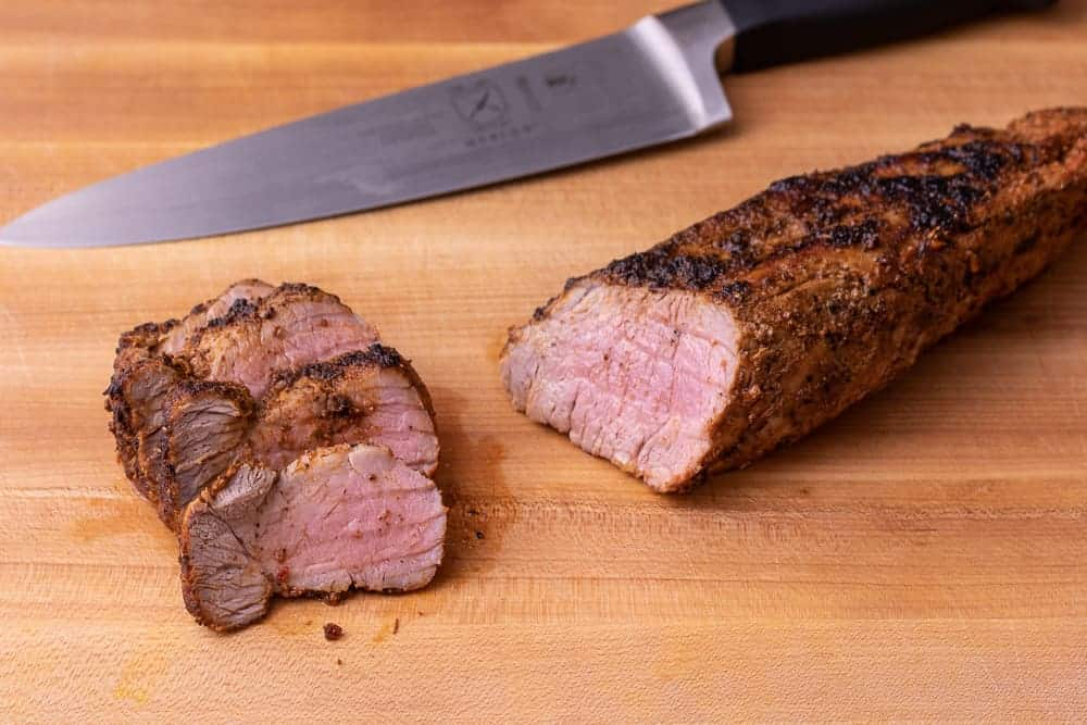 Close up shot of the pork tenderloin being cut by a large chef knife.