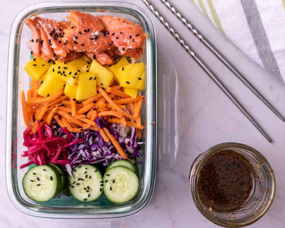 Salmon Poke bowl in a rectangular meal prep container with chop sticks. Featuring cooked salmon, fresh mango, matchstick carrots, pickled ginger, cabbage and cucumbers and sauce on the side.