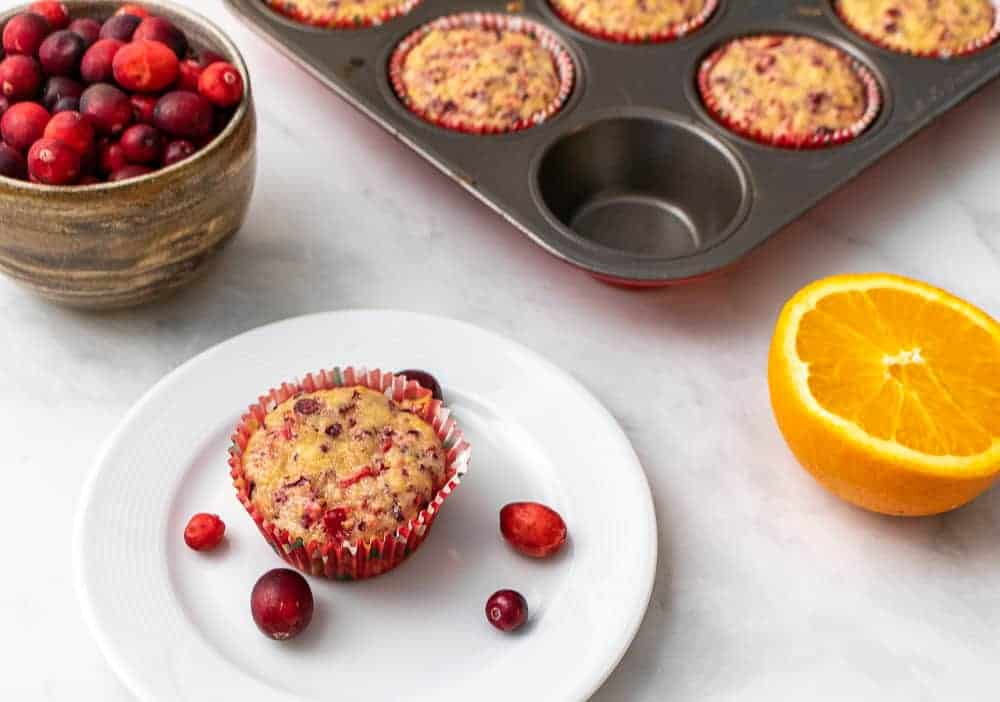 One muffin on a white plate in front of a tray of muffins, half an orange and a bowl of fresh cranberries.