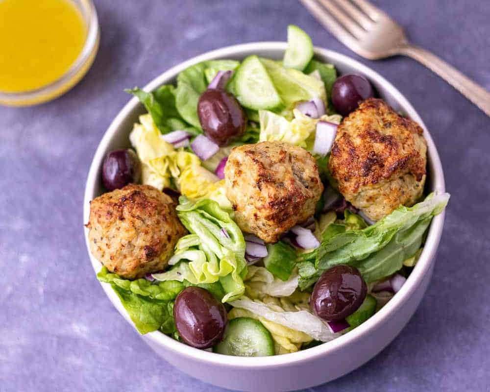 Greek chicken meatball salad in a bowl with a fork and dressing in the background