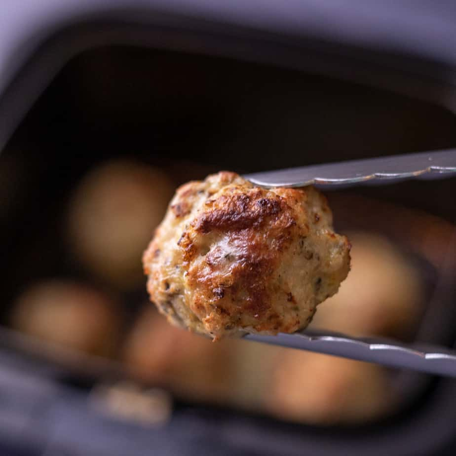 Closeup of greek meatball in tongs over the air fryer