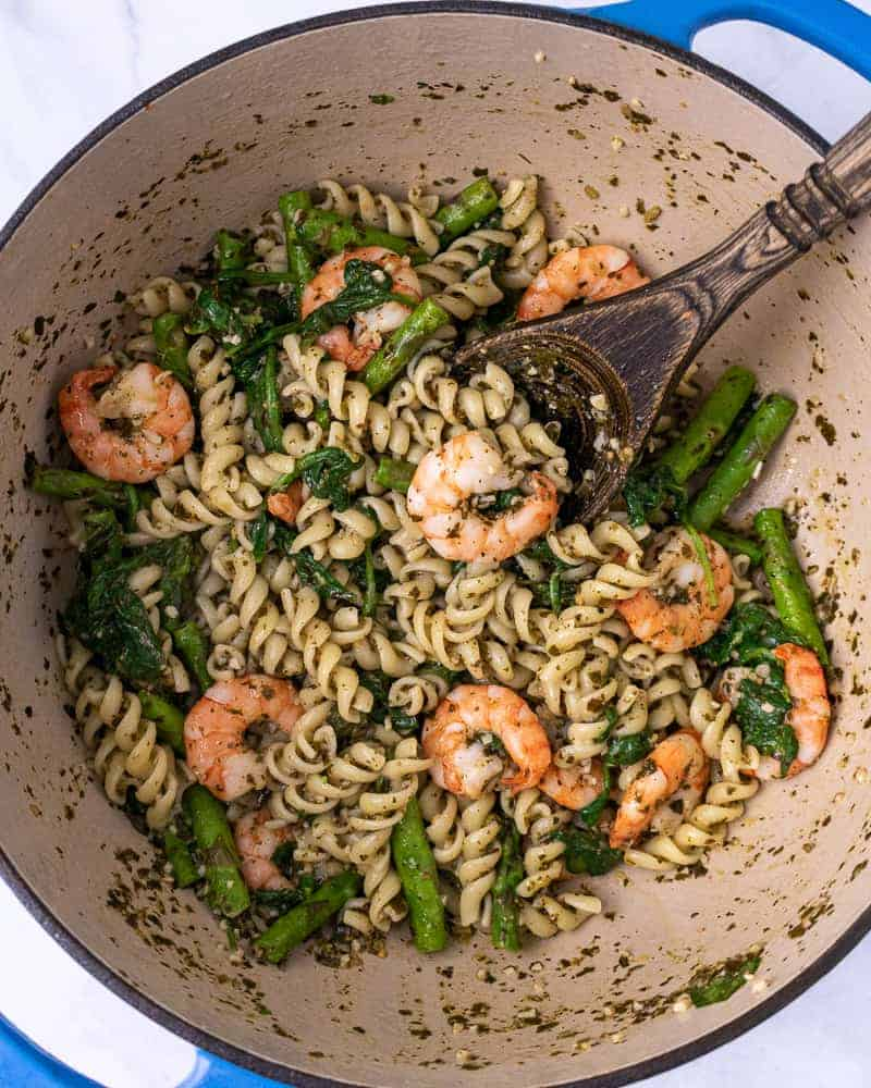 Lemon pesto pasta with shrimp mixed up in a dutch oven.