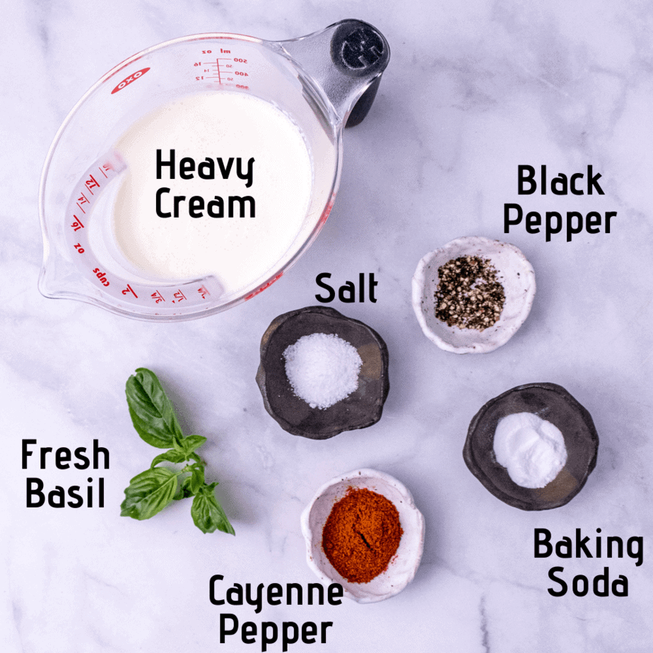 A white background with ingredients laid out with labels; heavy cream, black pepper, salt, fresh basil, baking soda and cayenne pepper.