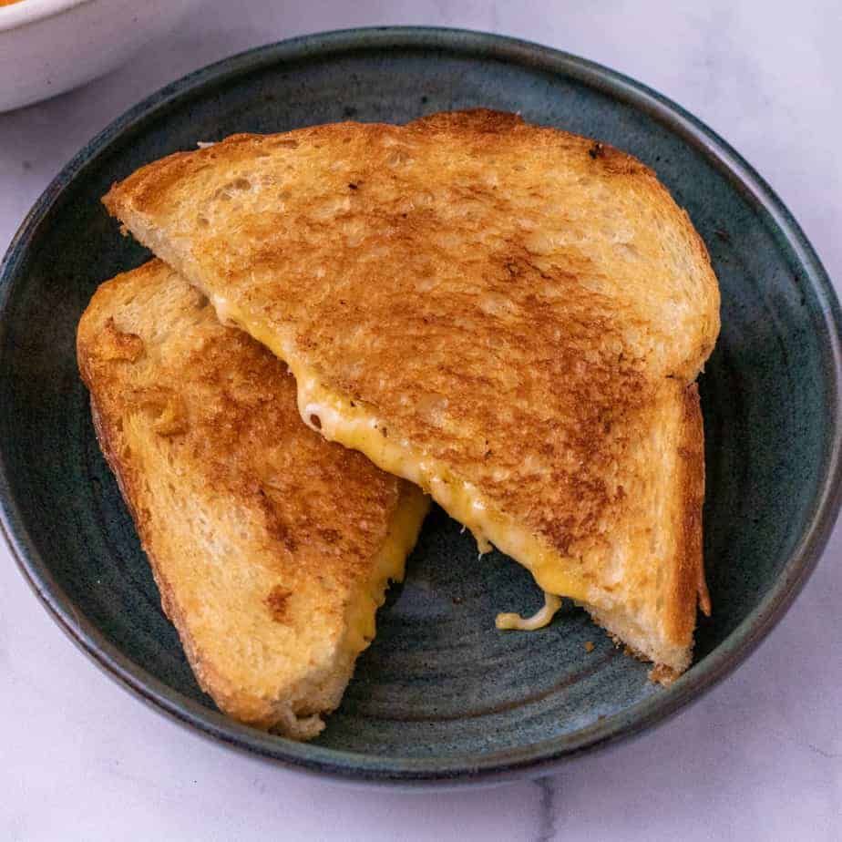 Grilled cheese sandwich cut diagonal on a green plate.