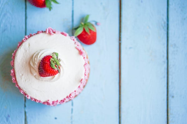 Strawberry cake with white cream on wooden background